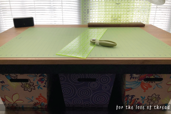 A self-healing cutting mat with ruler and rotary cutter sit on a table, a key supply in quilting.