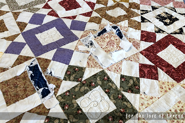 A quilt showing ripped seams and bare batting spaces.
