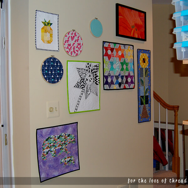 wall with several mini quilts hanging