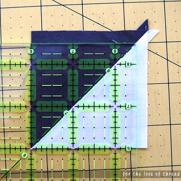 half-square triangle lined up on a ruler for the second cut