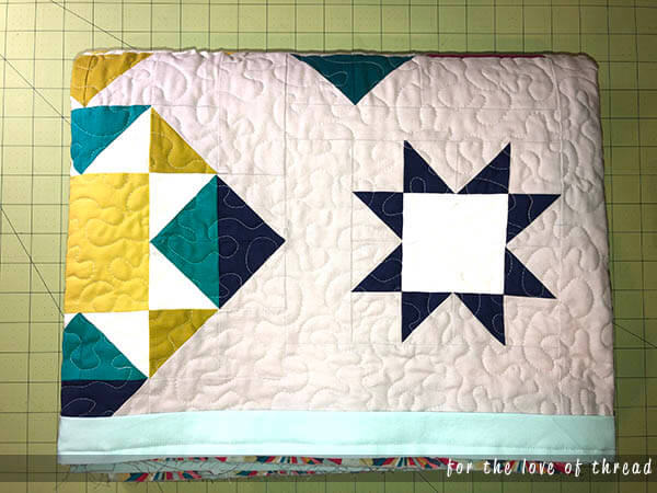 Perfect HST quilt folded on table