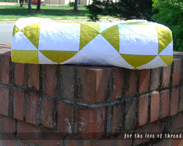 Wasabi Pickle quilt folded on top of a brick pillar