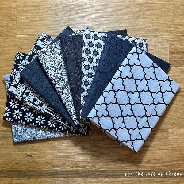 pile of black and white quilting fabrics on a wood table