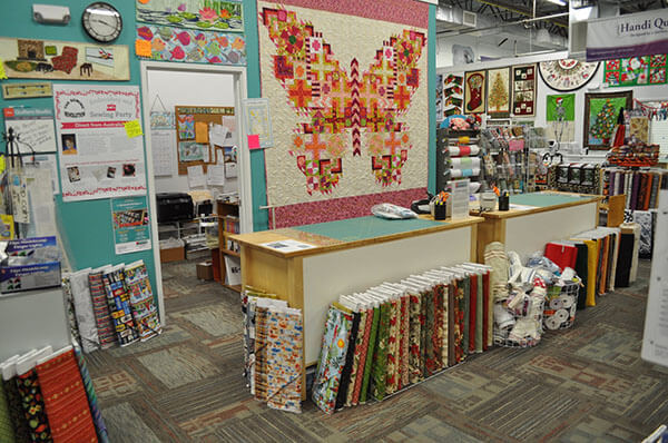 the cutting table in a quilt store with a butterfly quilt hanging on the wall behind it