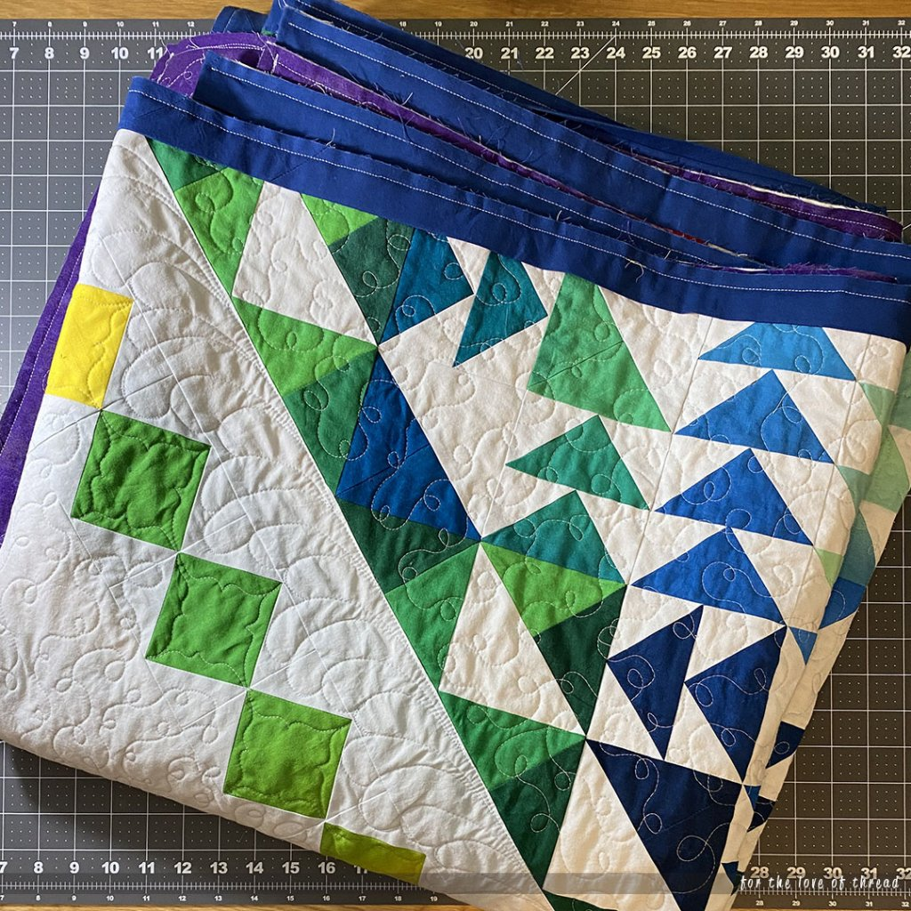 Dimensions quilt folded on a table with the binding attached.